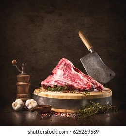 Raw dry aged t-bone beef steaks for grill with fresh herbs and cleaver