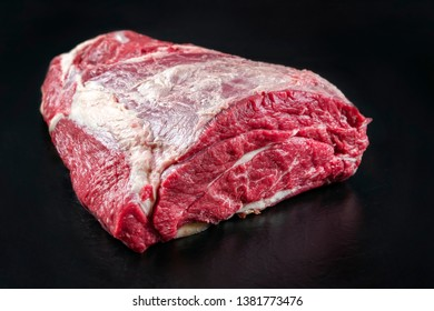 Raw dry aged wagyu beef shoulder clod roast as closeup on black background with copy space