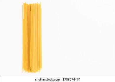 Raw dry spaghetti italian pasta spaghetti line texture yellow long spaghetti on white background. Concept food background.