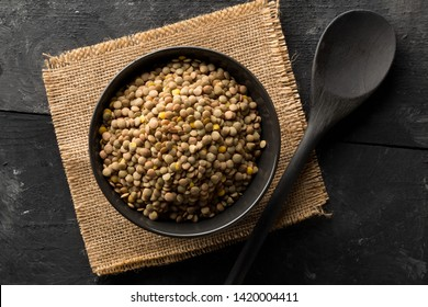 Raw, dry, uncooked brown lentil legumes in black bowl on rustic wood table background with selective focus top view flat lay from above