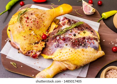 Raw duck legs. Fresh BIO ingredient for preparation traditional French confit. Spice, vegetable, herbs. Animal proteins and healthy fats, wooden board, stone background close up