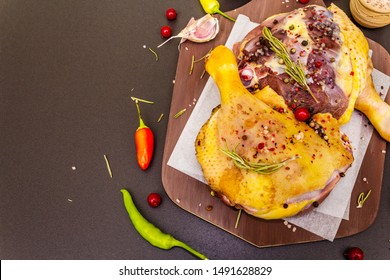Raw duck legs. Fresh BIO ingredient for preparation traditional French confit. Spice, vegetable, herbs. Animal proteins and healthy fats, wooden board, stone background copy space top view close up