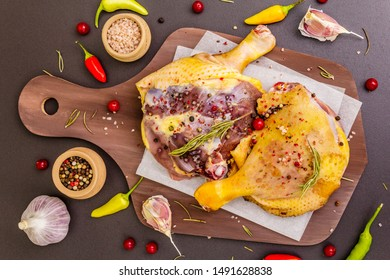 Raw duck legs. Fresh BIO ingredient for preparation traditional French confit. Spice, vegetable, herbs. Animal proteins and healthy fats, wooden board, stone background top view close up