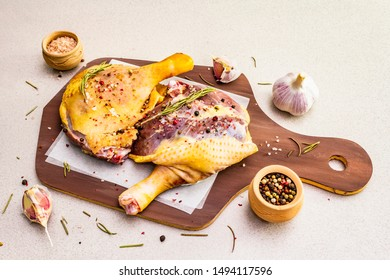 Raw duck legs. Fresh BIO ingredient for preparation traditional French confit. Rosemary, garlic, peppers mix, sea salt. Animal proteins and healthy fats, wooden board, stone background copy space