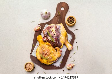 Raw duck legs. Fresh BIO ingredient for preparation traditional French confit. Spice, vegetable, herbs. Animal proteins and healthy fats, wooden board, stone background copy space, top view