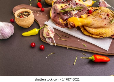 Raw duck legs. Fresh BIO ingredient for preparation traditional French confit. Spice, vegetable, herbs. Animal proteins and healthy fats, wooden board, stone background copy space
