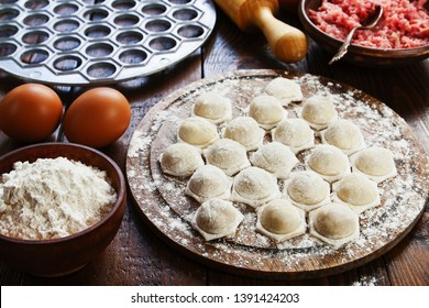 Raw dumplings with meat on a wooden table