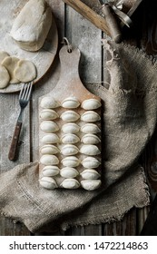 Raw dumplings on a wooden board. Traditional homemade food. The process of making dumplings. Slavic traditional dish. Dough for dumplings. Potato dumplings. Flour. View from above.