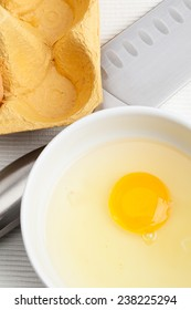 Raw egg in a white bowl.