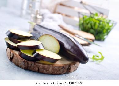 raw eggplant and knife on board, fresh eggplant