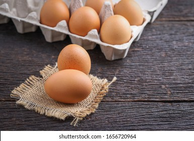 Raw eggs in egg box on rustic wooden background.