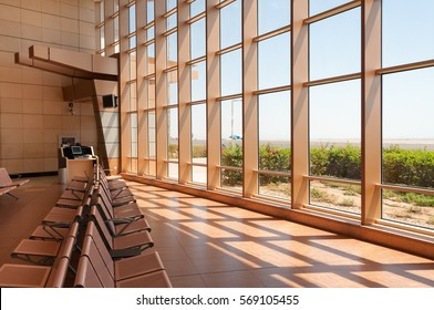 Raw of empty seats in airport waiting area near gate and big window