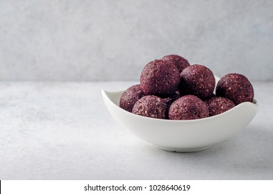 Raw energy balls with acai berry powder in white bowl on a light table. Horizontal image, copy space, front view