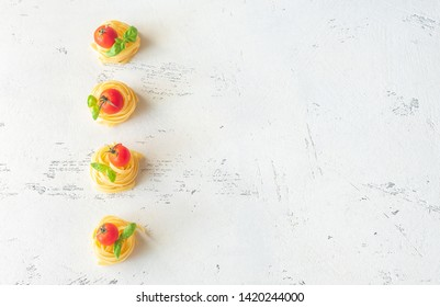 Raw fettuccine with cherry tomatoes and fresh basil leaves on the white background