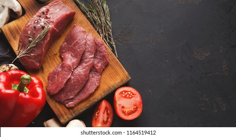 Raw filet mignon steaks. Fresh beef meat, rosemary on wooden board at black background. Organic ingredients for restaurant meals, vegetables, copy space