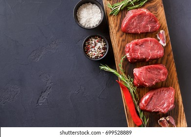 Raw filet mignon steaks with herbs and spices. Cooking ingredients for restaurant dish. Fresh meat, salt, rosemary, garlic and chilli pepper on wooden board at black background, copy space, top view