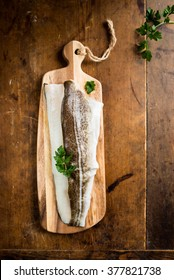 Raw fillet of Atlantic cod on a wooden cutting board on a vintage wooden table