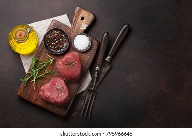 Raw fillet steak cooking on stone table. Top view with space for your text