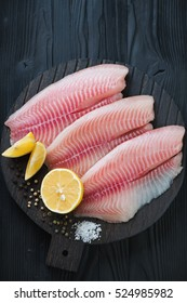 Raw fillet of tilapia fish on a black wooden cutting board, high angle view