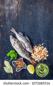 Raw fish Cooking background, fish on the black old wooden rustic table.Preparations to smoke, top view. Healthy food or diet concept