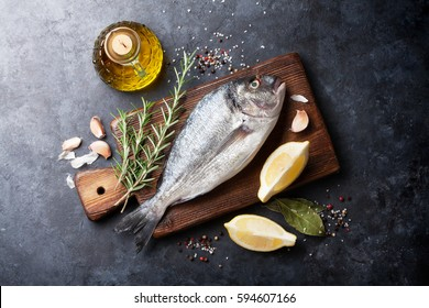 Raw fish cooking and ingredients. Dorado, lemon, herbs and spices. Top view on stone table