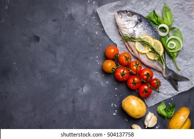 Raw fish with fresh ingredients ready to cook. Fish, lemon, herbs, potato, tomatoes. Ingredients for cooking on dark rustic background. Space for text. Diet and healthy food. Fish background. Top view