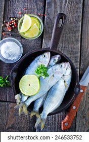 raw fish with lemon on the pan and on a table