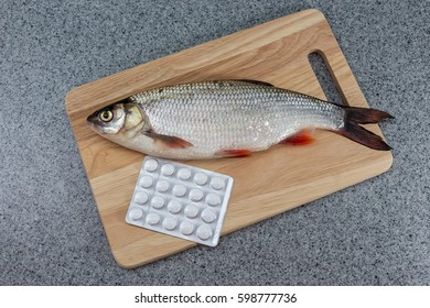 Raw fish, not cooked. Fish on a cutting Board, lay next to the pills. Symbolizes allergic to fish or the contamination of food, unnatural food. Or the risk of infection when consuming fish.