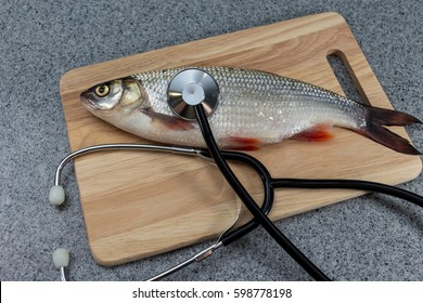 Raw fish, not cooked. Fish on a cutting Board, lying next to a stethoscope. The doctors recommend. Symbolizes allergic to fish or artificiality of food or the risk of infection when consuming fish.