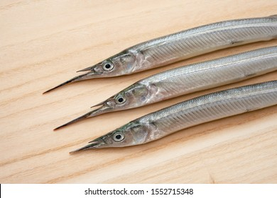 """Raw fish on a cutting board. The name of this fish is """"Sayori"""" in Japan."""