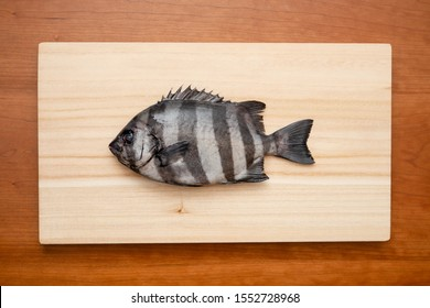 """Raw fish on a cutting board. The name of this fish is """"Striped beakfish""""."""