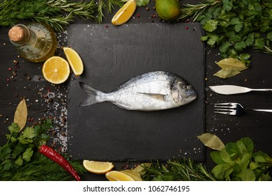 Raw fish on slate board with salt and herbs with lemon slices