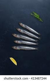 Raw fish with rosemary and lemon on dark background