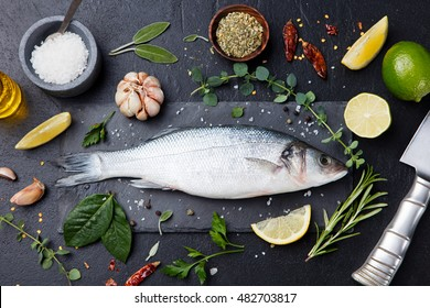 Raw fish, sea bass on slate black board. Ingredients for cooking, grill, roasting. Top view
