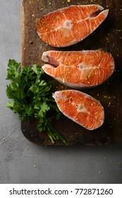 Raw fish steaks on wood board, food above
