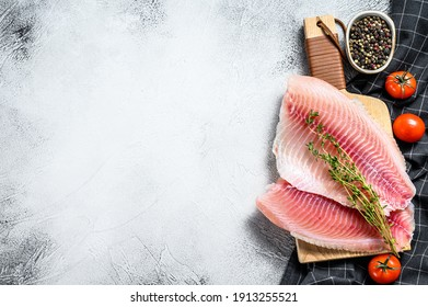 Raw fish tilapia on the cutting Board. Gray background. Top view. Copy space