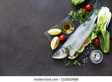 Raw fish with vegetables, herbs and spices. Sea bass. Overhead view