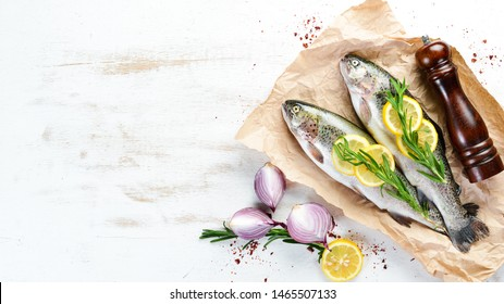 Raw fish with vegetables on a white wooden background. Fish trout. Top view. Free space for your text.