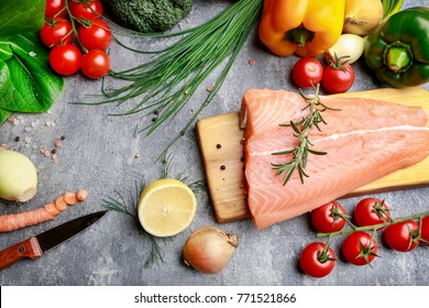 Raw fishes and vegetables on stone background, copy space.