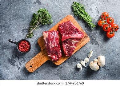 Raw flap steak flank cut with Machete, Skirt Steak, on woods chopping board, with herbs tomatoes peppercorns over grey stone surface background top view