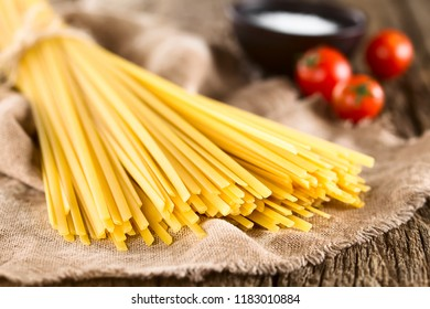 Raw flat long ribbon pasta called Fettuccini, salt and cherry tomatoes in the back (Very Shallow Depth of Field, Focus on the front of the pasta strands)