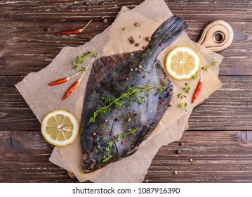 Raw flounder plaice fish (flatfish). Cooking process concept. Flounder fish with spices, lemon slices, thyme on parchment paper. Dark wooden table background. Top view.