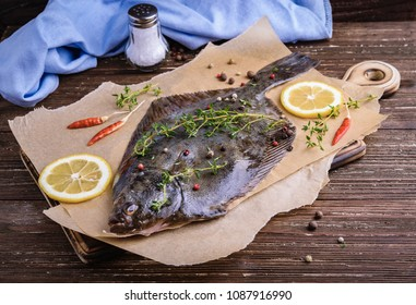 Raw flounder plaice fish (flatfish). Cooking process concept. Flounder fish with spices, lemon slices, thyme on parchment paper. Dark wooden table background.