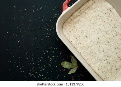 Raw focaccia dough in a baking dish. Traditional Italian Focaccia with  rosemary and bay leafs - homemade flat bread focaccia.