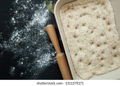Raw focaccia dough in a baking dish. Traditional Italian Focaccia with  rosemary, rolling pin and bay leafs - homemade flat bread focaccia.
