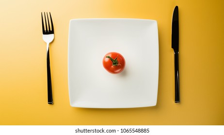 Raw food diet - a red tomato on a dining plate with utensils next to it.