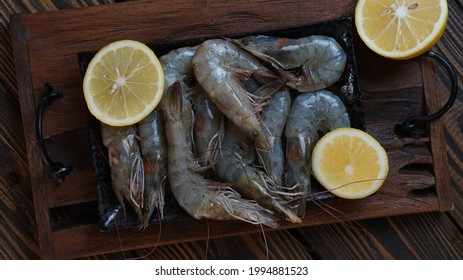 Raw food - shrimps with lemon on wooden background