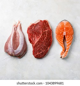 Raw food turkey meat, beef meat and Salmon oily fish steak on white textured background