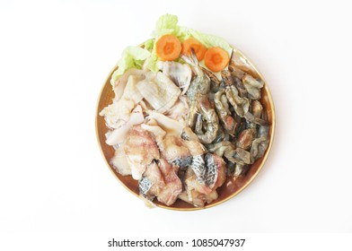 Raw foods: Fresh squid, white leg shrimp or pacific white shrimp (Litopenaeus vannamei, formerly Penaeus vannamei) and fish with chinese cabbage on plate isolated on white background, close up