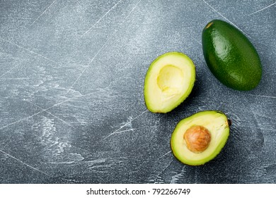 Raw fresh avocado cut into pieces on  dark old concrete or stone background. Selective focus.